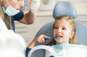 Child at Dentist, learning how to correctly brush her teeth