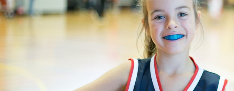 A young girl, in sport uniform, smiling at the camera and wearing a mouthguard