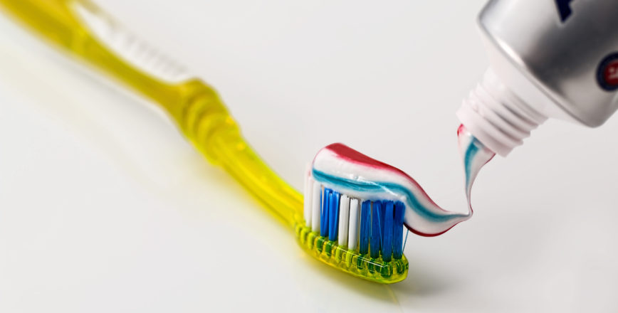 Toothpaste being put a yellow toothbrust